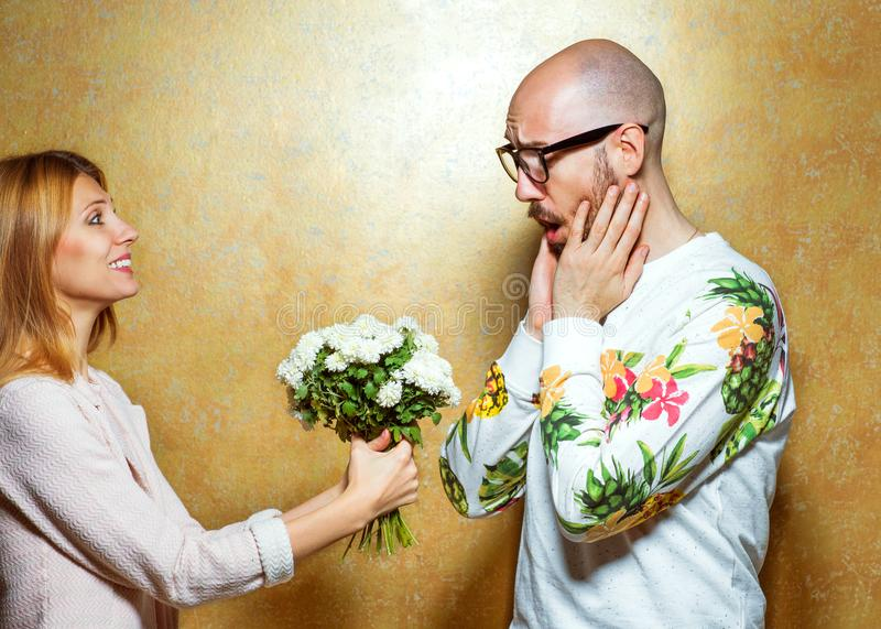 Emotional fashion couple give each other flowers on Valentine`s. Day. Vogue style stock image