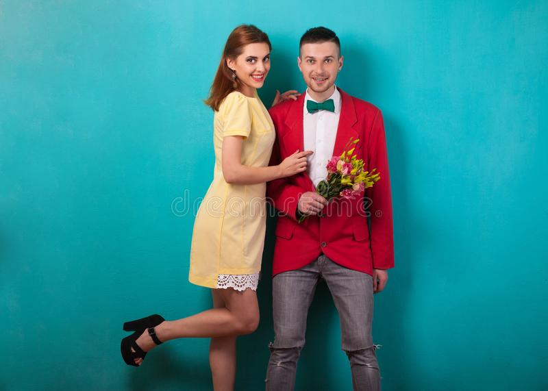 Emotional fashion couple give each other flowers on Valentine`s. Day. Vogue style royalty free stock photos