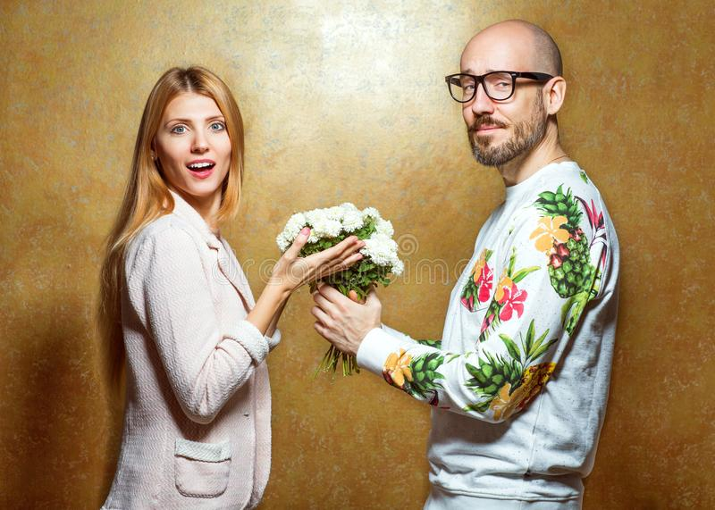 Emotional fashion couple give each other flowers on Valentine`s. Day. Vogue style stock images