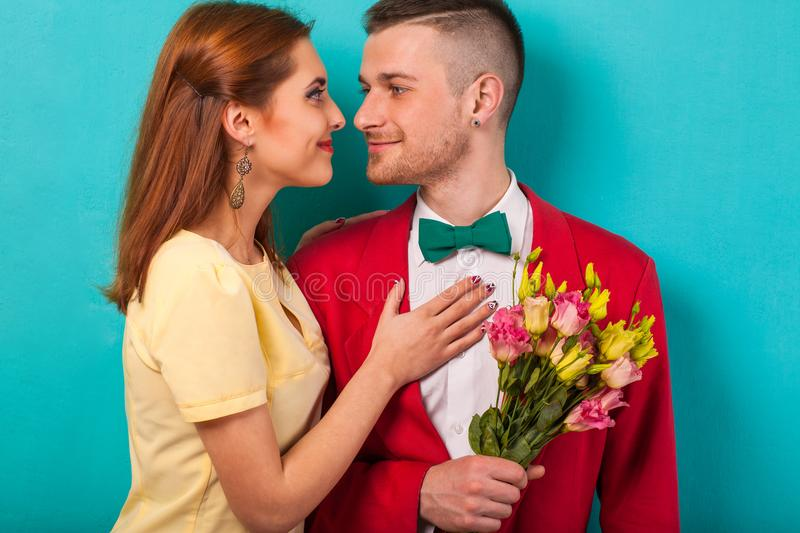 Emotional fashion couple give each other flowers on Valentine`s. Day. Vogue style royalty free stock photography