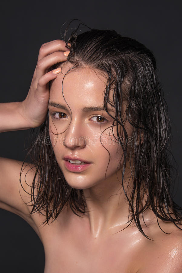 Emotional fashion portrait of beautiful women with bright makeup. Wet hair on her face. Studio photo on a black background. stock photo