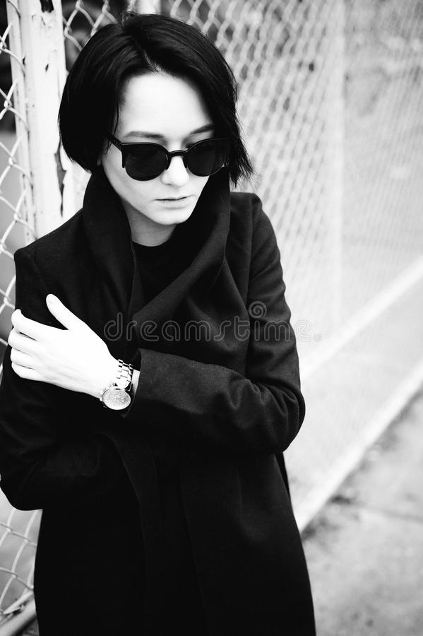 Emotional fashionable portrait of a young brunette woman in black clothes, jeans T-shirt, coat and sunglasses, in a Gothic style s. Ad mood stock photography