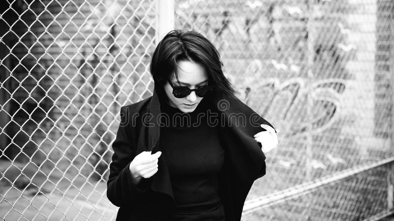 Emotional fashionable portrait of a young brunette woman in black clothes, jeans T-shirt, coat and sunglasses, in a Gothic style s. Ad mood stock images