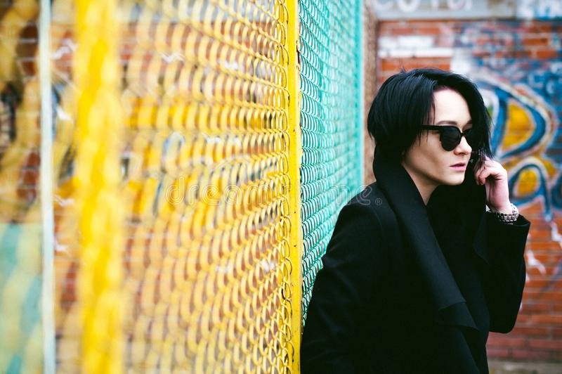 Emotional fashionable portrait of a young brunette woman in black clothes, jeans T-shirt, coat and sunglasses, in a Gothic style s. Ad mood stock photos
