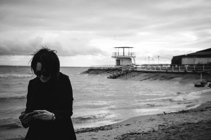 Emotional fashionable portrait of a young brunette woman in black clothes, jeans T-shirt, coat and sunglasses, in a Gothic style s. Ad mood royalty free stock image