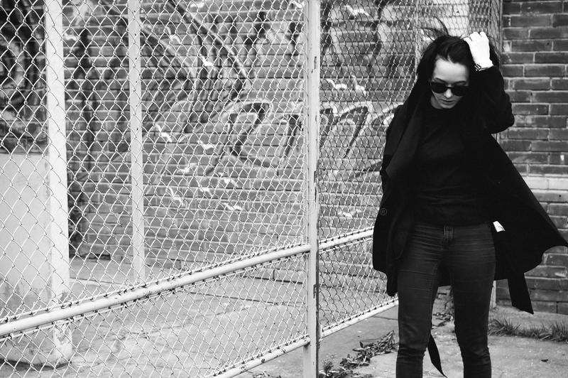 Emotional fashionable portrait of a young brunette woman in black clothes, jeans T-shirt, coat and sunglasses, in a Gothic style s. Ad mood stock image