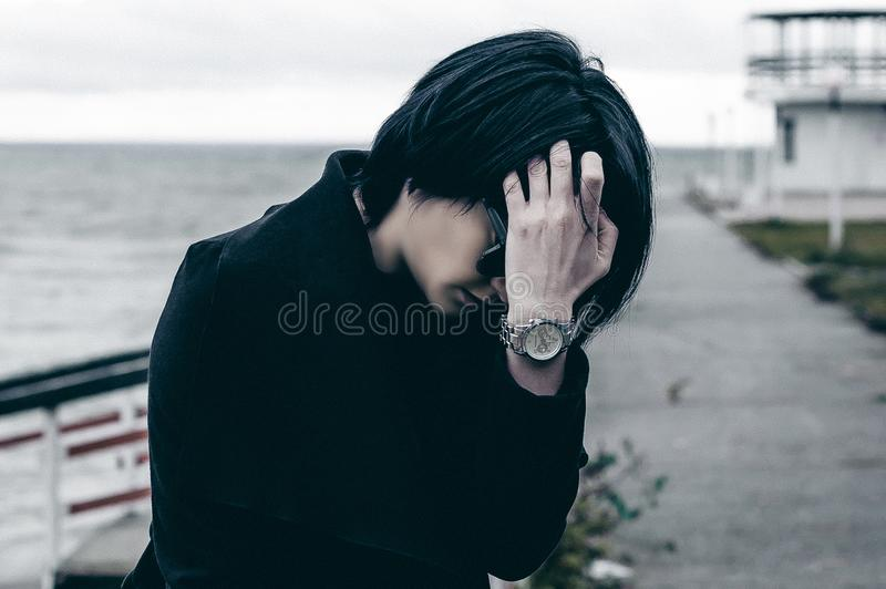 Emotional fashionable portrait of a young brunette woman in black clothes, jeans T-shirt, coat and sunglasses, in a Gothic style s. Ad mood. on an empty beach stock image