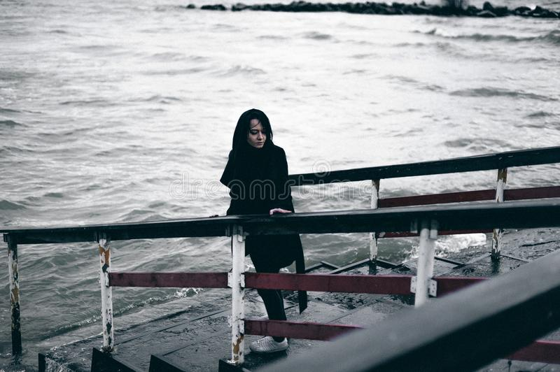 Emotional fashionable portrait of a young brunette woman in black clothes, jeans T-shirt, coat and sunglasses, in a Gothic style s. Fashionable portrait of a stock photo