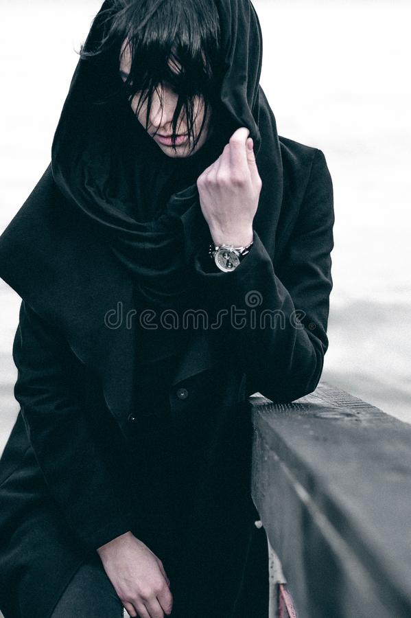 Emotional fashionable portrait of a young brunette woman in black clothes, jeans T-shirt, coat and sunglasses, in a Gothic style s. Ad mood. on an empty beach royalty free stock images