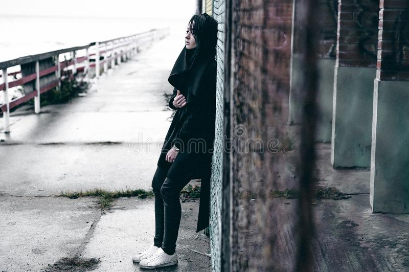 Emotional fashionable portrait of a young brunette woman in black clothes, jeans T-shirt, coat and sunglasses, in a Gothic style s. Fashionable portrait of a stock images