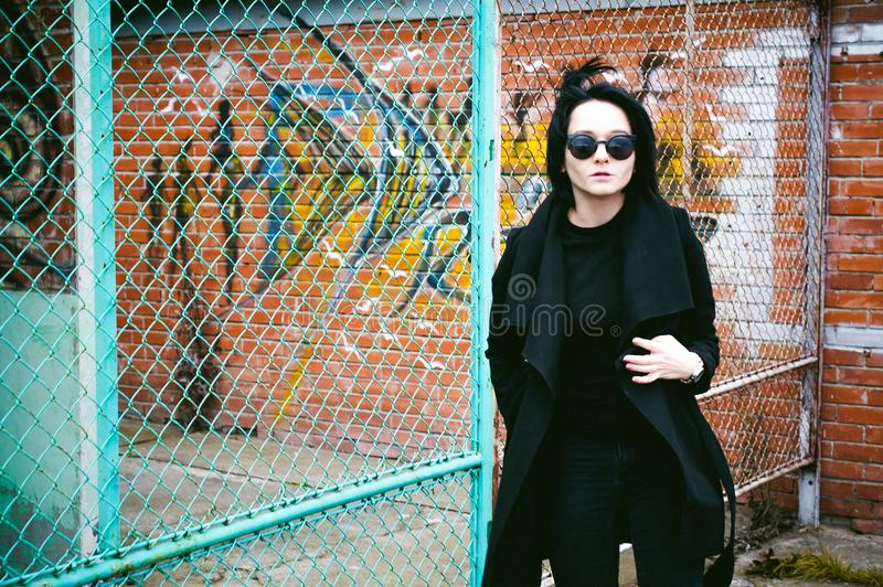 Fashionable portrait of a young brunette woman in black clothes, jeans T-shirt, coat and sunglasses, in a Gothic style sad mood. o. Emotional fashionable stock image