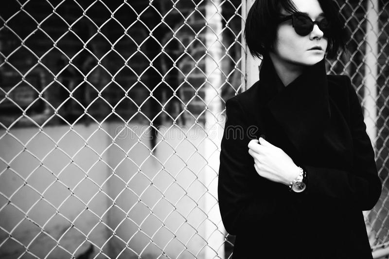 Emotional fashionable portrait of a young brunette woman in black clothes, jeans T-shirt, coat and sunglasses, in a Gothic style s. Ad mood. wrist watch royalty free stock image