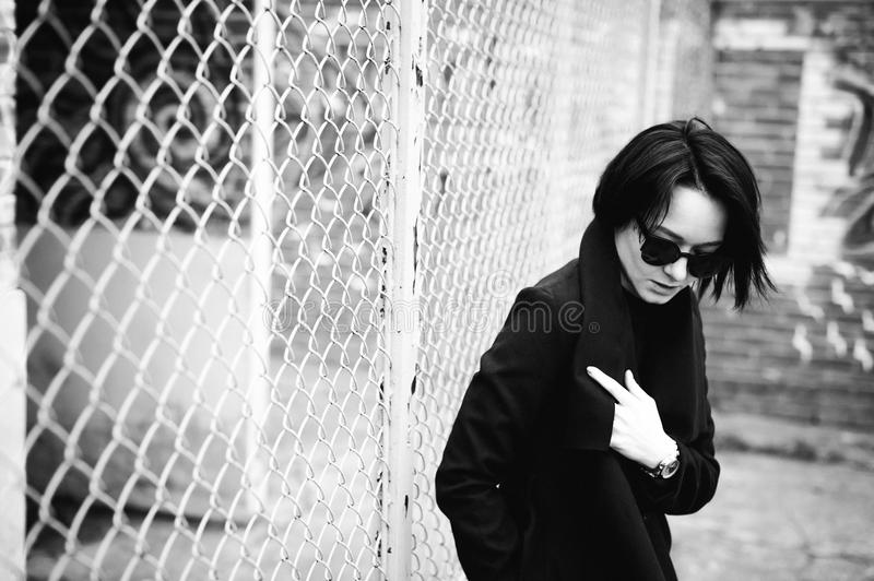 Emotional fashionable portrait of a young brunette woman in black clothes, jeans T-shirt, coat and sunglasses, in a Gothic style s. Ad mood royalty free stock photo