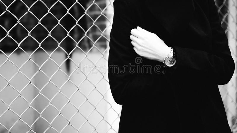 Emotional fashionable portrait of a young brunette woman in black clothes, jeans T-shirt, coat and sunglasses, in a Gothic style s. Ad mood. wrist watch stock photography