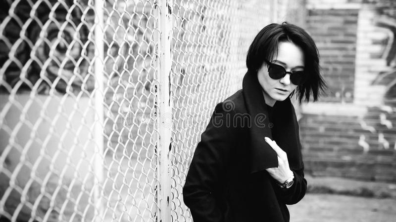 Emotional fashionable portrait of a young brunette woman in black clothes, jeans T-shirt, coat and sunglasses, in a Gothic style s. Ad mood royalty free stock images