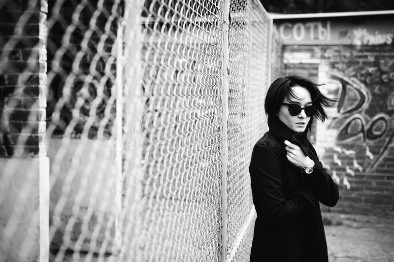 Emotional fashionable portrait of a young brunette woman in black clothes, jeans T-shirt, coat and sunglasses, in a Gothic style s. Ad mood royalty free stock photos