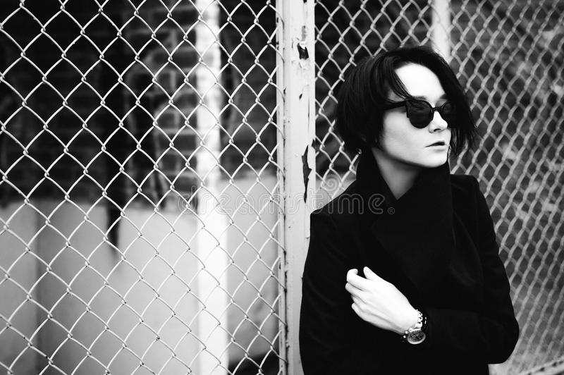 Emotional fashionable portrait of a young brunette woman in black clothes, jeans T-shirt, coat and sunglasses, in a Gothic style s. Ad mood. wrist watch stock images
