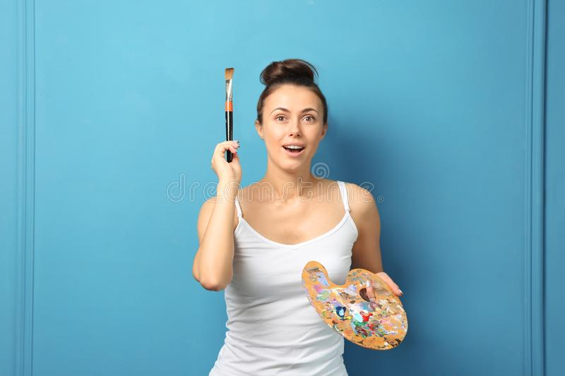Emotional female artist with brush and paint palette on color background stock photography