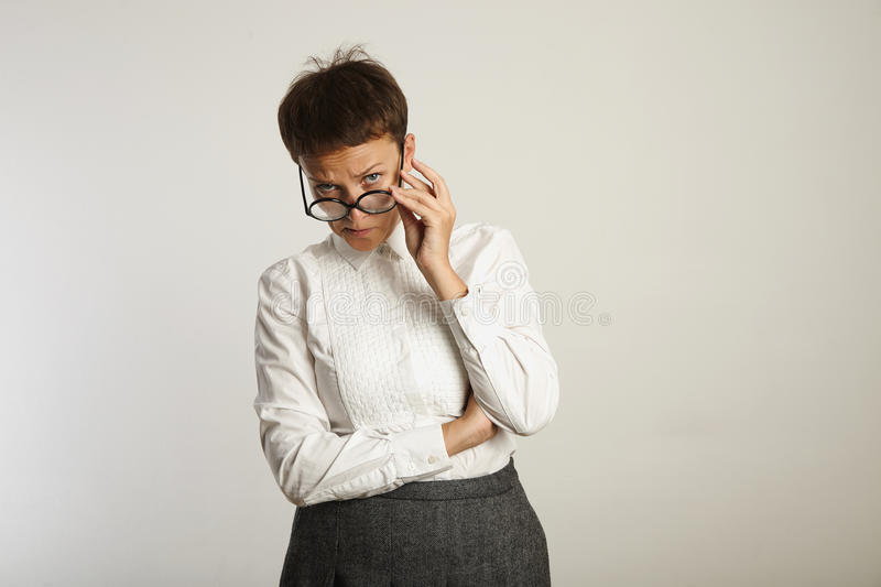 Emotional female teacher in glasses. Strict female teacher looks disapprovingly at the camera and adjusts her glasses royalty free stock photos