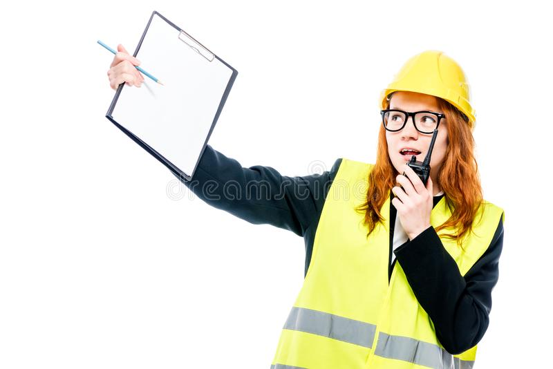 Emotional foreman with a walkie-talkie in a vest. And a yellow hard hat on a white background royalty free stock images