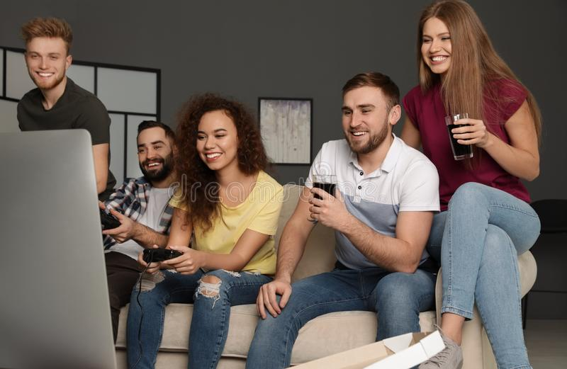 Emotional friends playing video games. At home stock photos