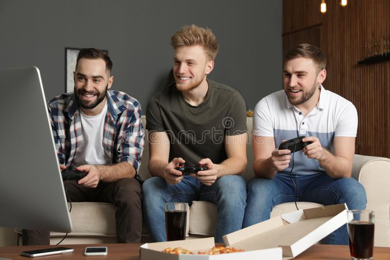 Emotional friends playing video games. At home royalty free stock photography