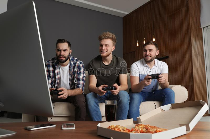 Emotional friends playing video games. At home stock photo