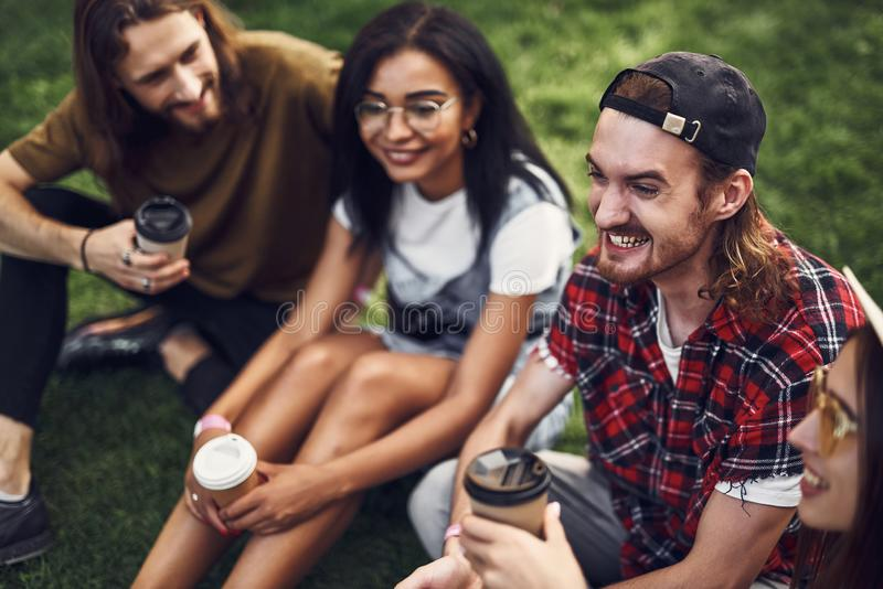Emotional friends sitting on the grass and looking happy royalty free stock photo