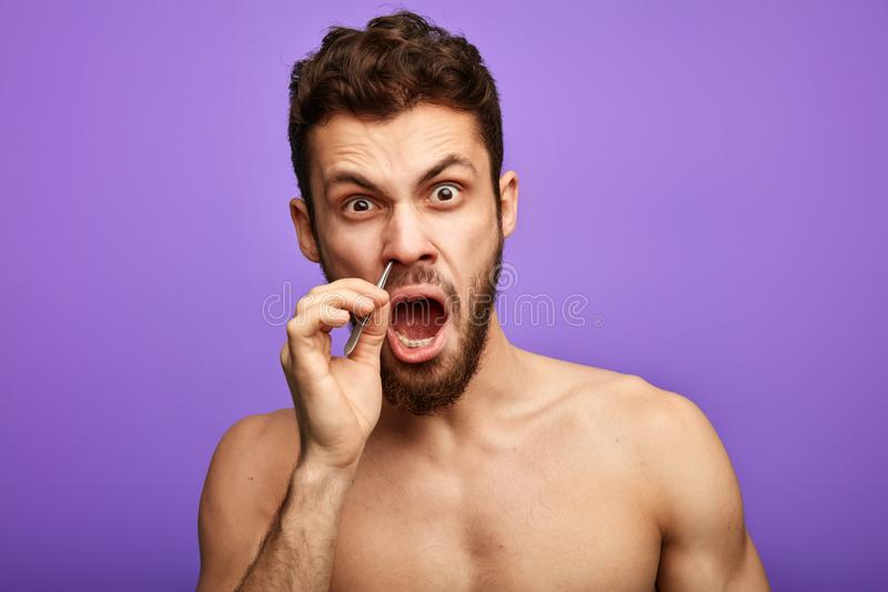 Emotional funny man pucking nose hair with tweezers. And looking at the camera. close up portrait royalty free stock images