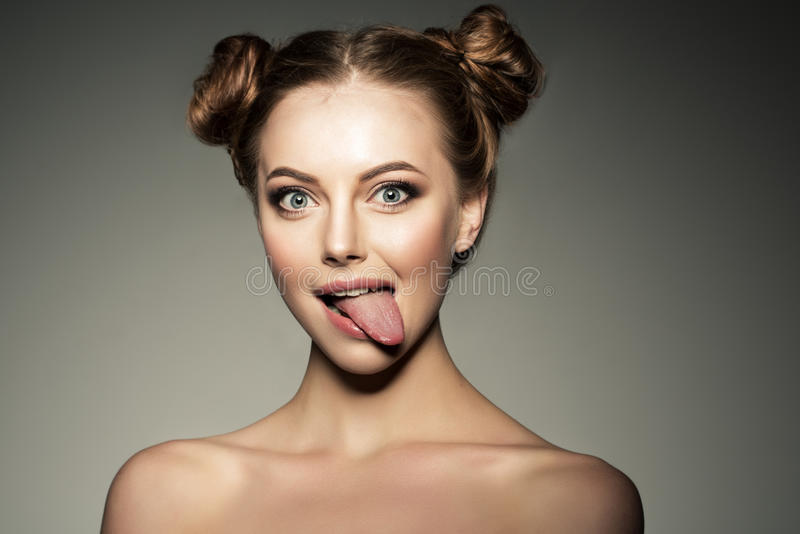 Emotional girl. Beautiful modern model shows tongue Positive woman hipster. Emotions on face. stock images