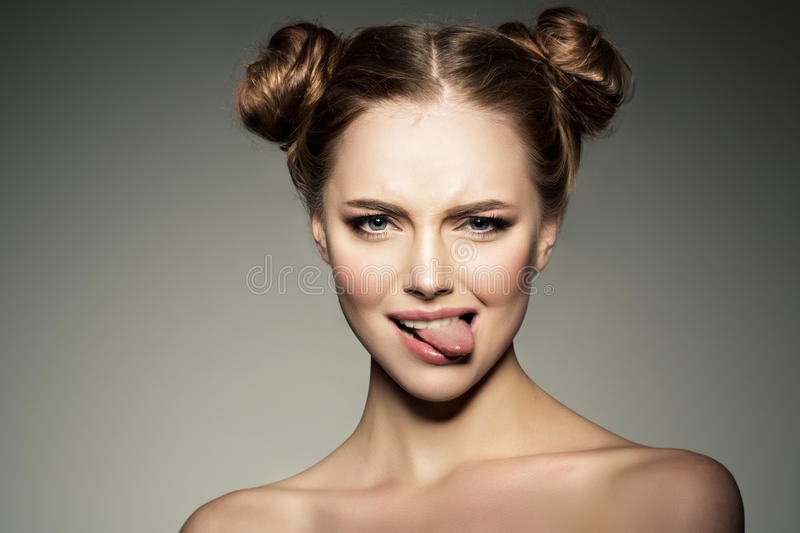 Emotional girl. Beautiful modern model shows tongue Positive woman hipster. Emotions on face. stock image