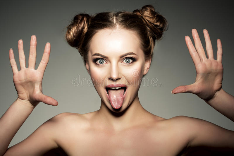 Emotional girl. Beautiful modern model shows tongue Positive woman hipster. Emotions on face. royalty free stock photos