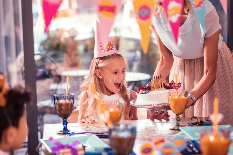 Emotional girl feeling excited while looking at her birthday cake royalty free stock photos