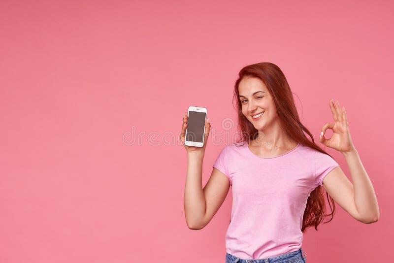 Emotional girl happily winked presure eyes, holding a mobile phone stock images