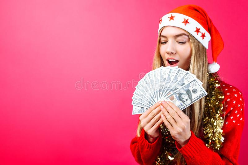 Emotional girl in a red sweater and Santa Claus hat, in admiration holding money on a red background. Christmas, business stock image