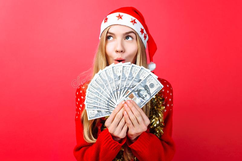 Emotional girl in a red sweater and Santa Claus hat, in admiration holding money on a red background. Christmas, business stock photo