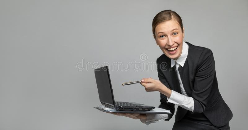 Girl in the office laughing pointing at laptop screen. Emotional girl working in the office. The joy and laughter of the girl Secretary in the office. not royalty free stock photos