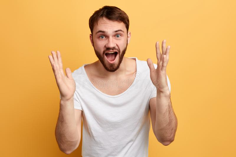Emotional happy man gesturing with raised hands triumphing or telling news. Emotional happy man gesturing with raised hands triumphing or telling incredible news stock photo