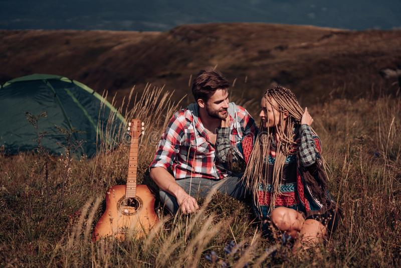 Emotional happy young loving couple on picnic hugging outside in free alternative vacation camping over mountains. royalty free stock images