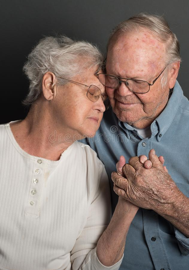 Emotional image of Senior couple holding hands in a tender loving embrace, both wearing glasses, man unshaven. Senior couple holding hands in a tender loving stock photography