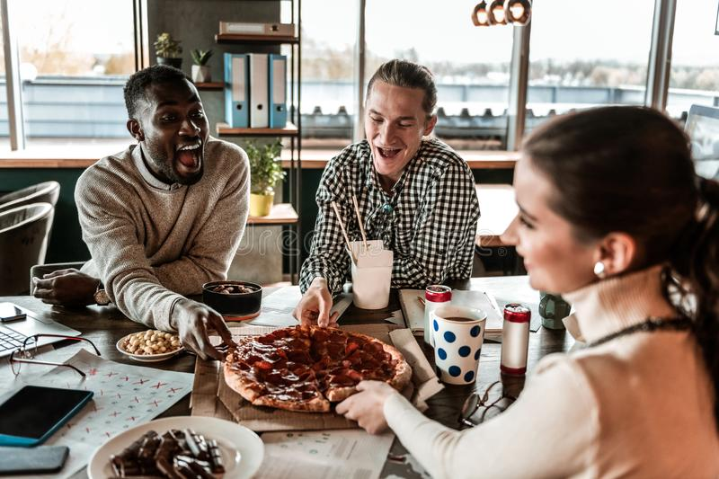 Emotional international man taking piece of pizza royalty free stock photography