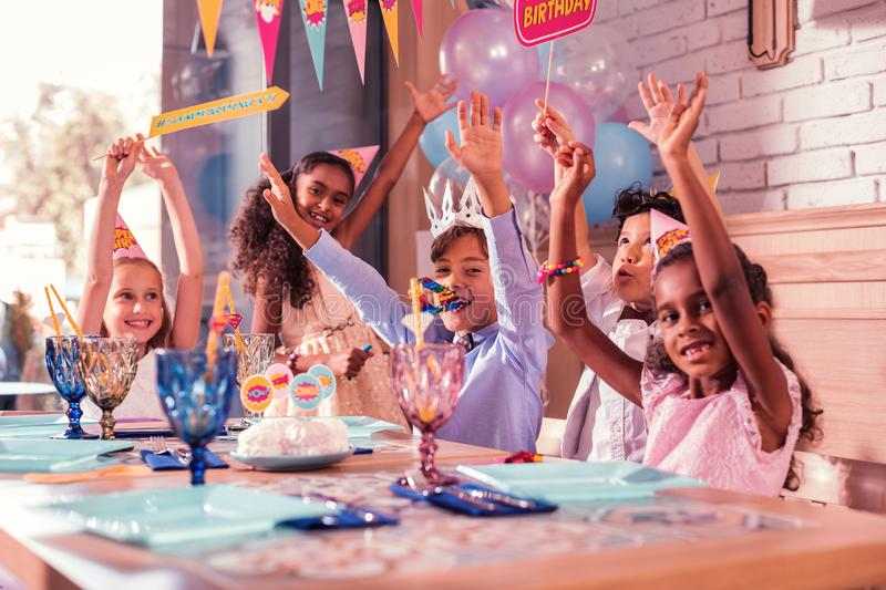 Emotional kids smiling and putting hands up at the party stock photography