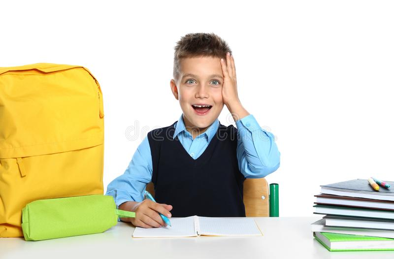 Emotional little boy in  with school stationery at desk against white background royalty free stock photos