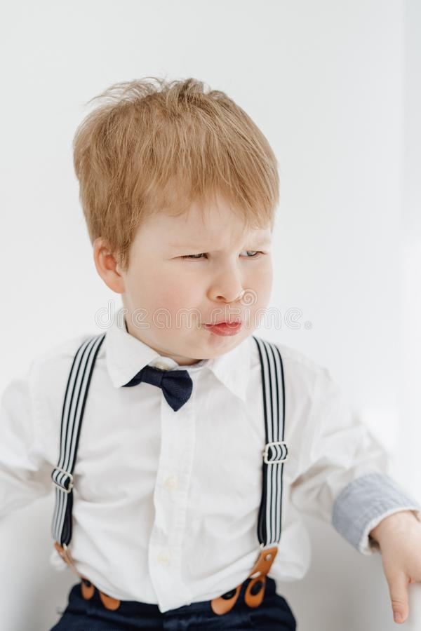 Emotional Little Caucasian Boy Grimace Portrait. Funny Redhead Child Sitting on Chair  on White Background. Kid Model with Scowly Face Frown. Adorable Toddler royalty free stock images
