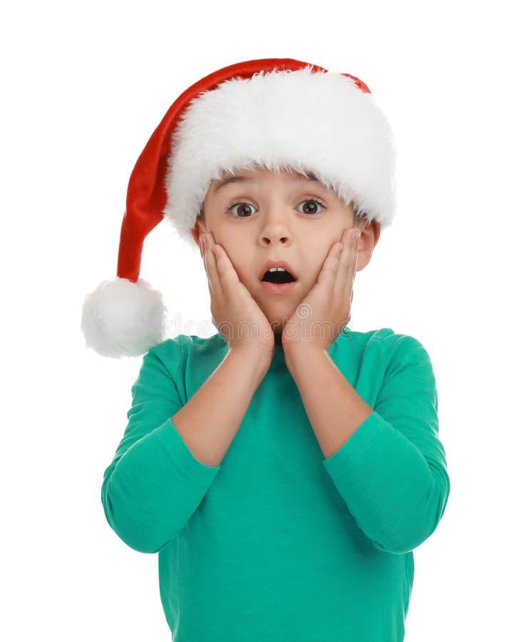 Emotional little child wearing Santa hat. Christmas holiday stock photo