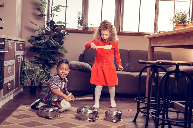 Emotional little female going to play with kitchenware. Join us. Handsome dark-skinned boy expressing positivity while posing on camera royalty free stock photo