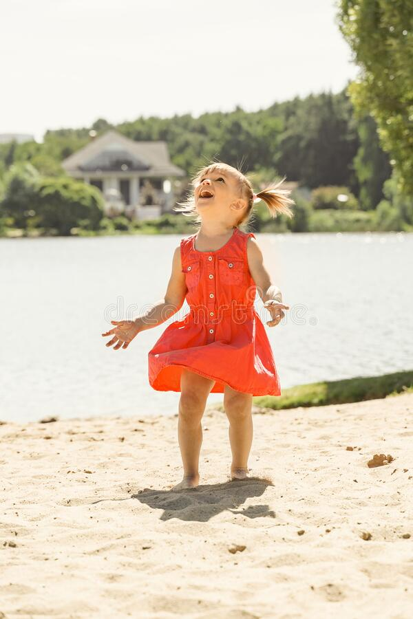 Free Emotional Little Girl In Red Dress Looks Up With Delight Stock Image - 198120501