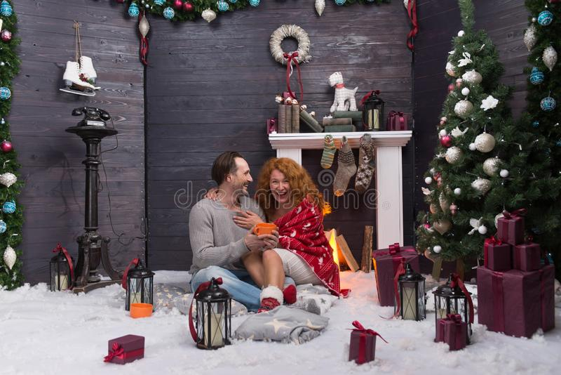 Two romantic people laughing while celebrating New Year near the fireplace. Emotional loving couple hugging near the fireplace in New Year interior and laughing royalty free stock images