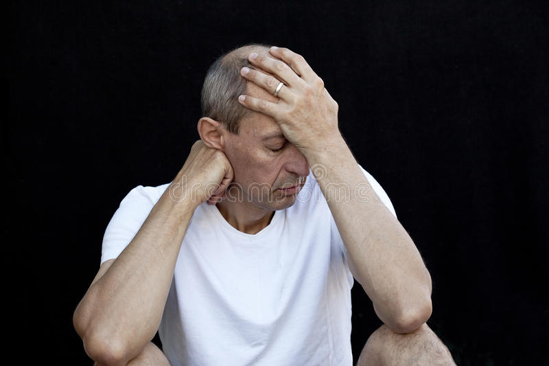 Emotional man. Cowering in grief against black background royalty free stock images