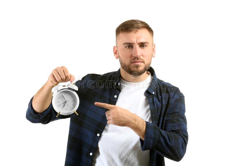 Emotional man with alarm clock on white background stock photo